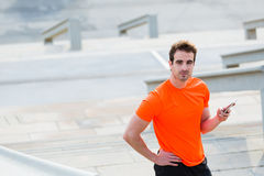 Young men runner using mobile phone while standing against steps background with copy space, Royalty Free Stock Images