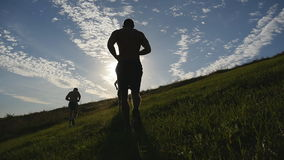 Young men running over green hill over blue sky background. Male athletes is jogging in nature at sunset. Sport runners