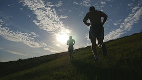 Young men running over green hill over blue sky background. Male athletes is jogging in nature at sunset. Sport runners stock video