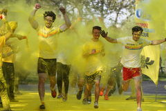 Young men running through yellow paint splatter Stock Photos