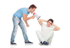 Young men screams to his friend through a megaphone Stock Images