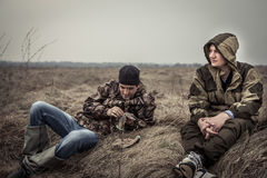 Young men with serene and peaceful expression in camouflage having rest in rural field relaxing on dry grass after long hunting da. Young men with serene and stock images