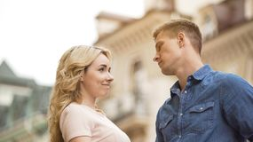 Young man seriously looking at girlfriend, woman late for date, apologetic look. Young men seriously looking at girlfriend, women late for date, apologetic look Stock Images