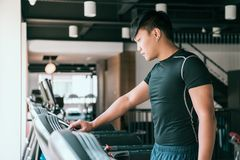 Male runner set up treadmill in gym stock images