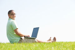 A young men sit on the in the park using a laptop Stock Photo