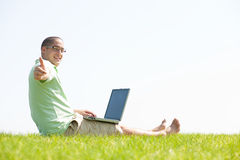 A young men sit on the in the park using a laptop Royalty Free Stock Photos