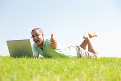 A young men sit on the in the park using a laptop Stock Images