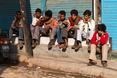 Young Men Sitting Along Street in Delhi, India. Street scene in Delhi, India royalty free stock photography