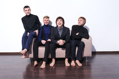 Young men sitting on a sofa laughing Stock Images