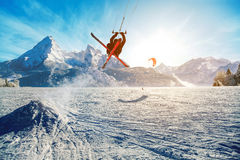 Young men, skiing on frozen lake in the mountains, in the rays of the rising sun, in winter Royalty Free Stock Images
