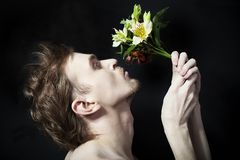 Young men sniffing bouquet of flowers Royalty Free Stock Photos