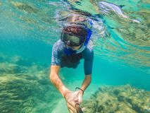 Young men snorkeling exploring underwater coral reef landscape background in the deep blue ocean with colorful fish and. Young man snorkeling exploring royalty free stock photo