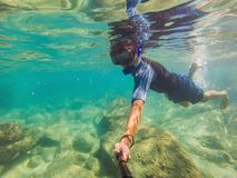 Young men snorkeling exploring underwater coral reef landscape background in the deep blue ocean with colorful fish and. Young man snorkeling exploring royalty free stock image