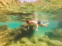 Young men snorkeling exploring underwater coral reef landscape background in the deep blue ocean with colorful fish and. Young man snorkeling exploring stock photos