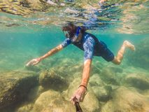 Young men snorkeling exploring underwater coral reef landscape background in the deep blue ocean with colorful fish and. Young man snorkeling exploring stock photography