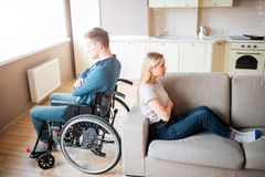 Young man with special needs and healthy woman sit back to back in room. Argue and quirrel. Worker with disability and stock image