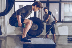 Young men in sportswear exercising at gym workout. Muscular young men in sportswear exercising at gym workout stock images