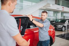 Young men stand by red car and hold its front door opened. He looks at seller with confidence. Guy in white shirt. Stretches his hand royalty free stock images