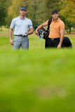 Young men standing on golf course carrying bags Stock Photography