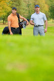 Young men standing on golf course carrying bags Stock Images