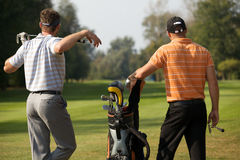 Young men standing in golf course by golf bag full of sticks royalty free stock image