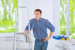 A young men standing near the stepladder holding color palette a Royalty Free Stock Photos