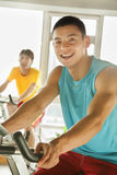 Young men on stationary bikes exercising in the gym Royalty Free Stock Photos