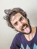 Young men sticking out her tongue Royalty Free Stock Image