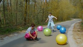Guys dancing street dance. Young men street dancers in goggles with colorful balls in the forest. Slow motion of happy guys in bright ski suits among of bright stock video
