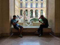 Young men study cell phones on window seat in Louvre Royalty Free Stock Images