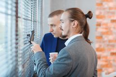 Young men in suits near a large office window. stock photos