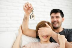Man surprising woman with a key of their new house. Young men surprising women with a key of their new house. Male closing his girlfriend eyes. Feeling of royalty free stock image