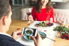 Young couple having romantic dinner in the restaurant salad photos. Young men taking photos of his meal and women having romantic dinner in the restaurant eating Stock Images