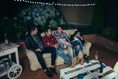 Young men talking and drinking in a party Stock Images