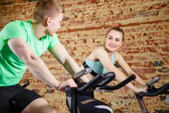 Young man talking to a cute blonde while they both do some cardio on a bicycle at the gym. Focus on woman. Young men talking to a cute blonde while they both do Royalty Free Stock Photos
