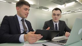 Young men talking, using laptop and tablet in large company. Two people discuss information they see on screen of black gadget and silvery pc, gesticulating stock video footage