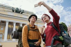 Young man and teenager girl - tourists - taking selfies against the Bolshoi theatre in Saint-Petersburg, Russia