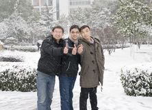 Young men thumbs up in snow. Three young man with coats  smile thumbs up  in snow day in winter Royalty Free Stock Image