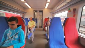 Young men travel in comfort chairs on electric train. Motion along aisle past young men traveling in comfort chairs on fast electric train with brightly lit stock video footage