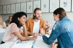 Young man and two girls working together in office. Group of students studying together in classroom. Group of cool stock photo