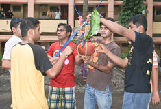Young men tying a pot of butter during Janmasthami. Young men tying an earthen pot containing butter to a high hanging rope during Dahi Handi event of royalty free stock photo