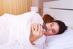 Man using his mobile phone in bed while his wife is sleeping nex Royalty Free Stock Images