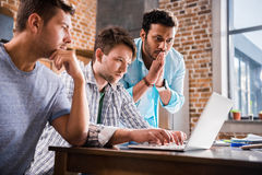 Young men using laptop together at home, young professional group concept Stock Photo