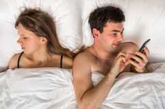 Young man using mobile phone, while his wife sleep at night Stock Photos