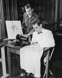 Young men using sewing machine Stock Images