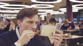 Young men using smartphone and drinking coke at food court in shopping mall. Portrait. HD stock video footage