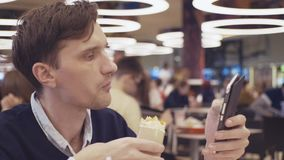 Young men using smartphone eat Shawarma roll at food court in shopping mall. Portrait. Young men using smartphone eat hamburger at food court in shopping mall stock video footage