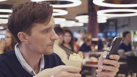 Young men using smartphone eat Shawarma roll at food court in shopping mall. Portrait. Young men using smartphone eat hamburger at food court in shopping mall stock footage