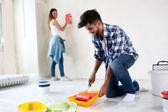 Man using take color with roller to painting house. Young men using take color with roller to painting house Royalty Free Stock Images