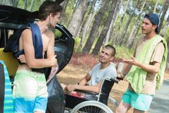 Young men by vehicle in forest one in wheelchair Royalty Free Stock Photography
